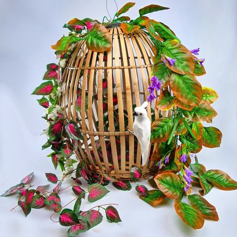 "Bamboo Parrot Cage, approx. 32"" tall by 25"" diameter. Dressed with artificial tropical foliage, flowers and parrot by our chic in-house stylist"